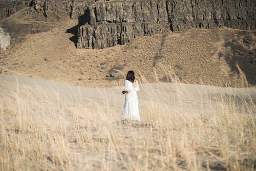 Female in white dress walking in nature near rocky cliffs