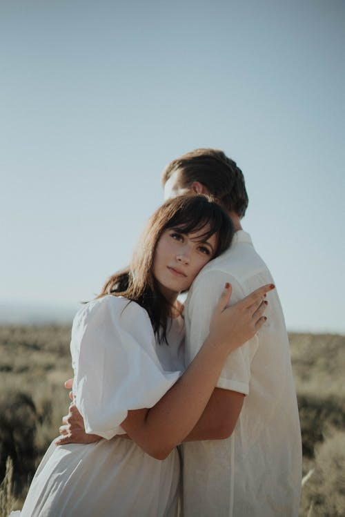 Calm female in light dress embracing and leaning on shoulder of boyfriend while standing in field in countryside in sunny day