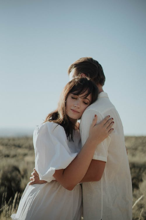 Young couple hugging in rural field