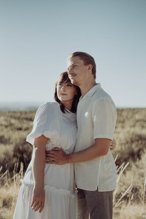 Young romantic couple hugging in rural field and looking away in sunny summer day