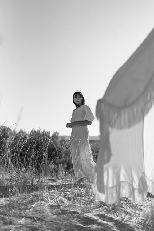 Full body of young woman in long white dress standing beside white tent in rural field in summer