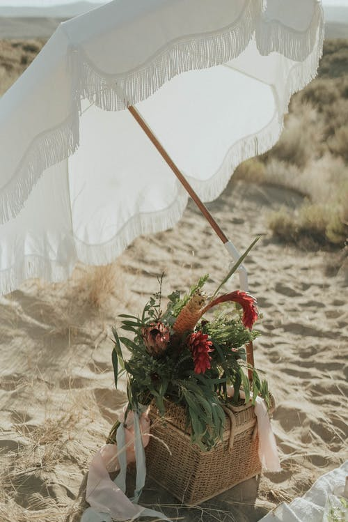 Basket with flowers and umbrella on sandy beach
