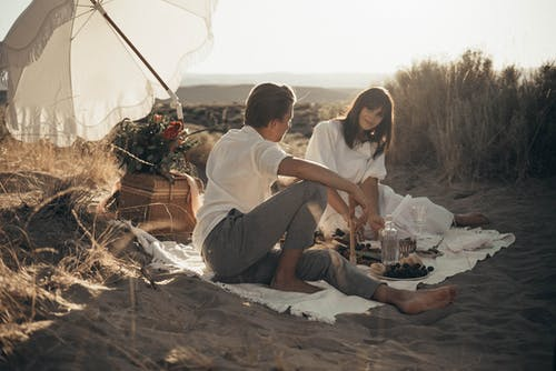 Young loving couple having romantic picnic sitting on white blanket with food and drinks under white umbrella