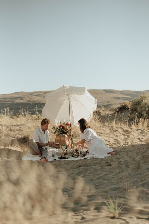 Young couple in white clothes sitting together on sandy dune and having picnic under white umbrella