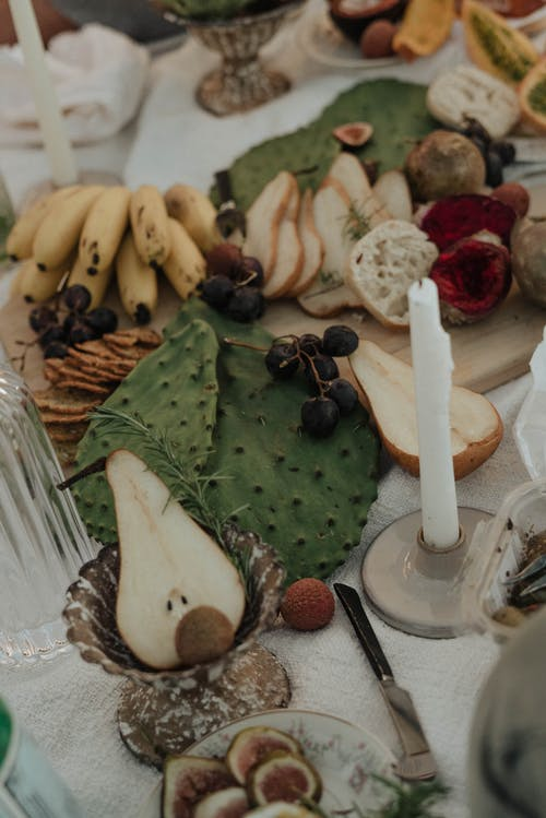 From above of fresh fruit and bread prepared for picnic on white cloth decorated with candles and opuntia