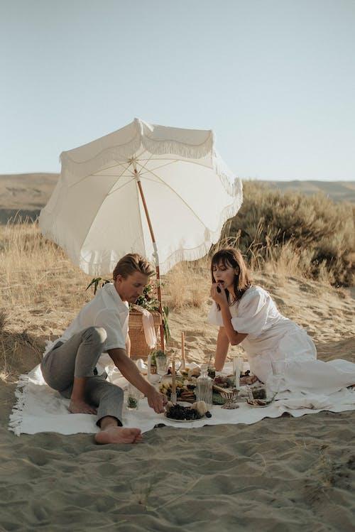 Young couple having picnic on sandy terrain