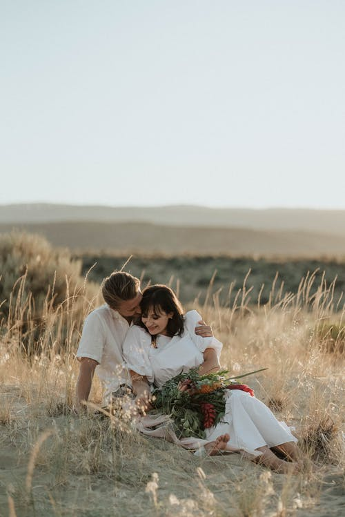 Happy young couple sitting on grassy meadow and embracing while spending summer holidays together in countryside