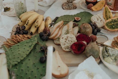 From above of fresh fruit with snacks green opuntia and bread on white cloth for picnic