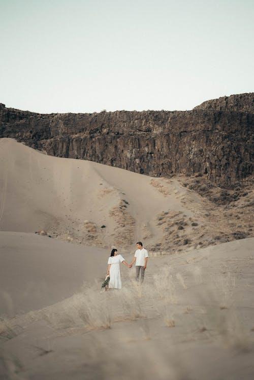 砂の上を歩く男と女