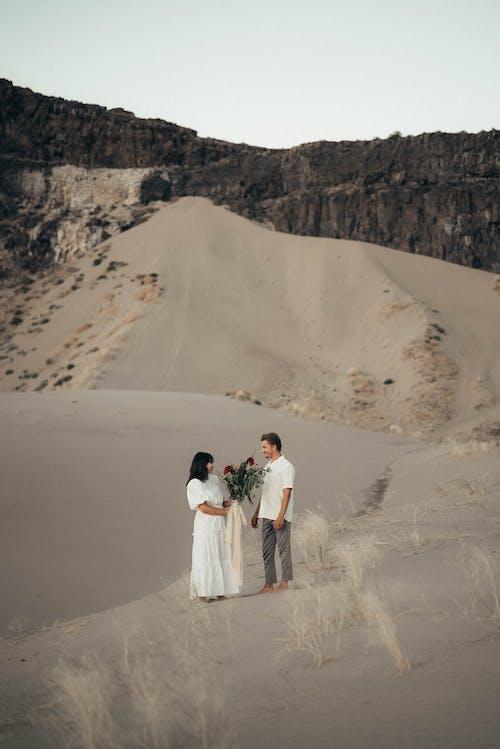 Мужчина и женщина, держась за руки во время прогулки по песку