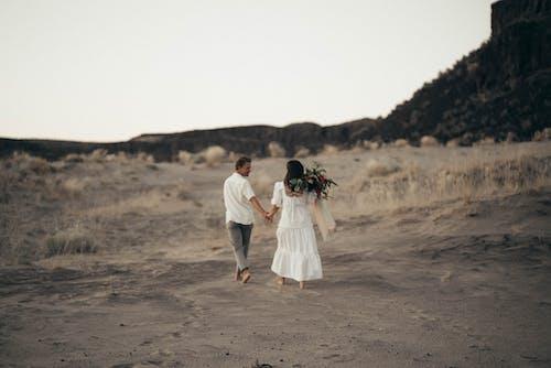 茶色の砂の上を歩きながら手をつないで男と女
