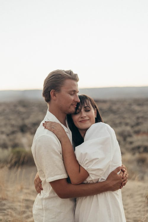 Happy couple embracing gently in grassy field in savanna