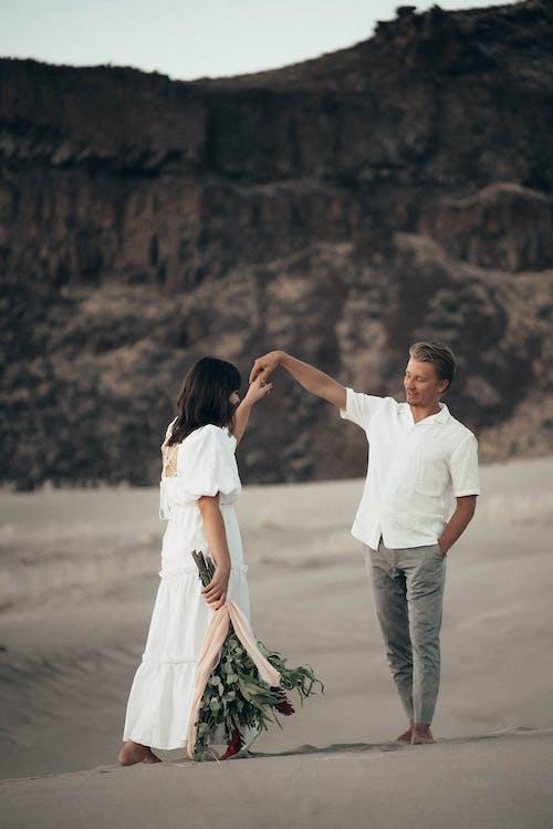 白いドレスシャツの男と茶色の砂の上を歩く白いドレスの女性