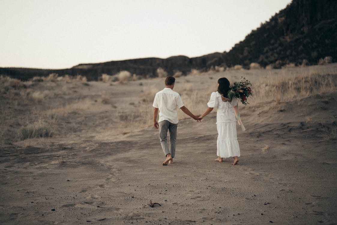 Full body back view of anonymous bride with flowers and groom holding hands while strolling on sandy field during wedding celebration