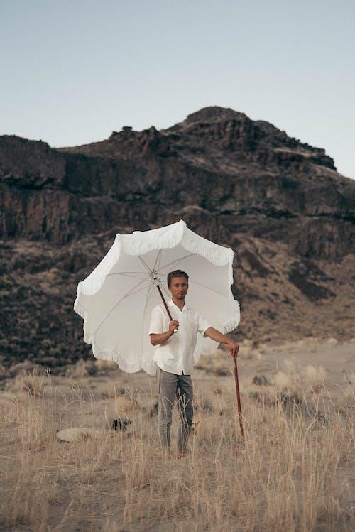 Женщина в белой рубашке с длинным рукавом с зонтиком