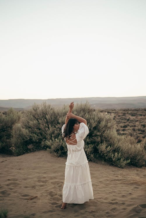 Full body back view of barefoot anonymous female in elegant white dress standing on dry ground near bushes while dancing with raised arms