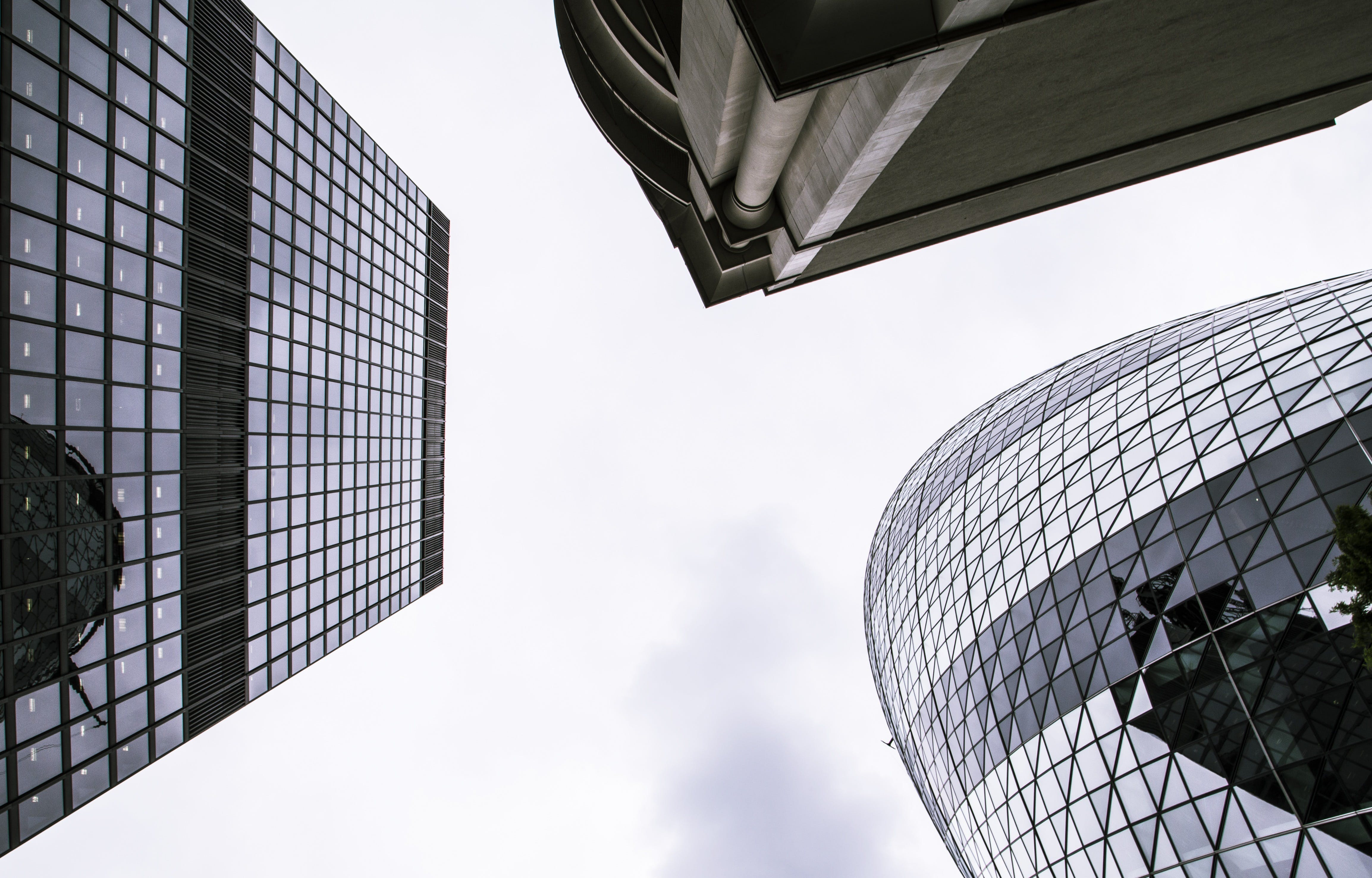 Worm's Eye View of Mirror Covered Concrete Buildings Under Gray Cloudy Skies
