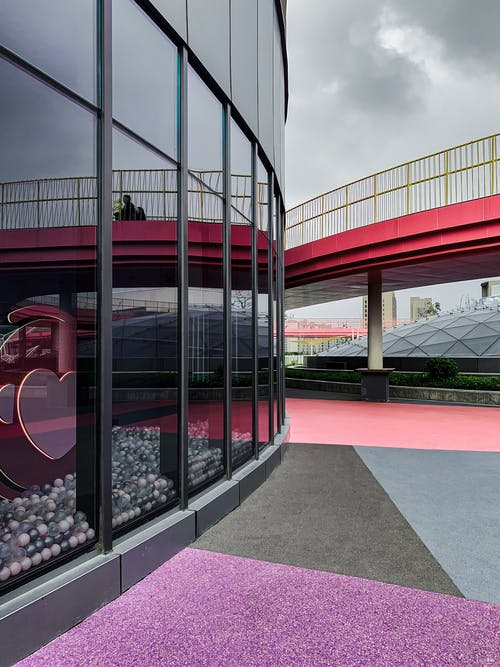 Exterior of glass building facade on city street with colorful geometric ground and pink bridge under cloudy sky