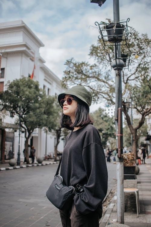 Woman in Black Coat Wearing Black Sunglasses and Green Hat Standing on Sidewalk