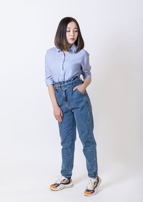 Woman in Blue and White Striped Button Up Shirt and Blue Denim Jeans