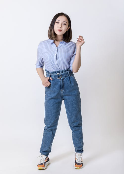 Woman in Blue Denim Jeans and White and Black Stripe Shirt