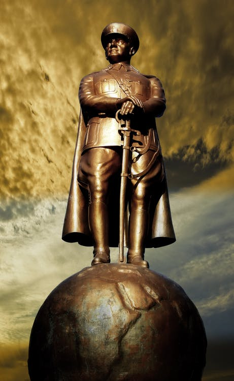 Man in Coat Statue on Globe