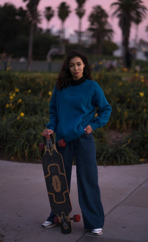 Female skater standing in street in day