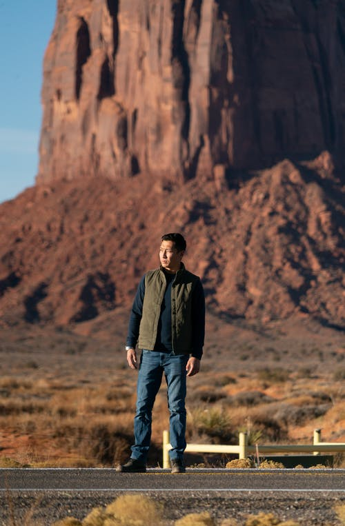 Man standing near mountain in desert