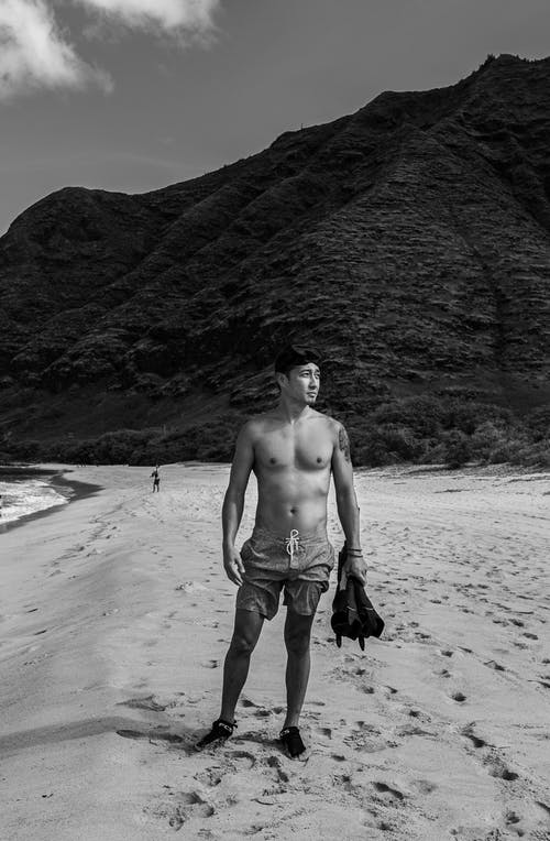Black and white full body Asian male with naked torso standing on sandy beach against rocky formation and looking away
