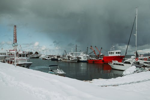 Seashore covered with snow near sea with various ships and yachts against overcast sky in port in cold winter day
