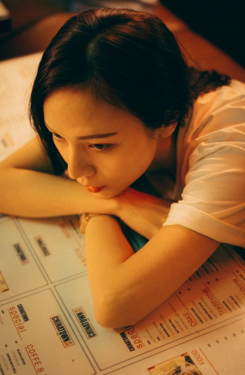 From above of young pensive ethnic female leaning with hands on menu while looking away at cafeteria table