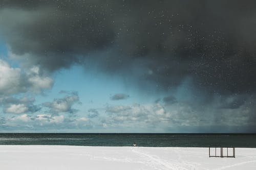 Coast covered with snow near calm endless sea against gray clouds on blue sky in winter time in cold nature