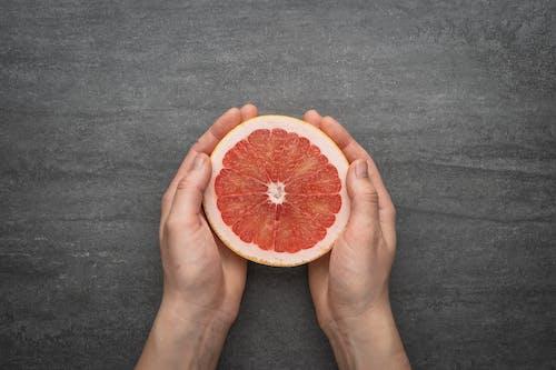 スライスしたオレンジ色の果物を持っている人