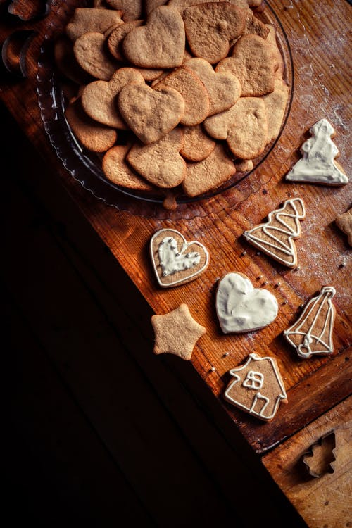 High angle of tasty homemade gingerbread cookies in different forms placed on wooden table at home