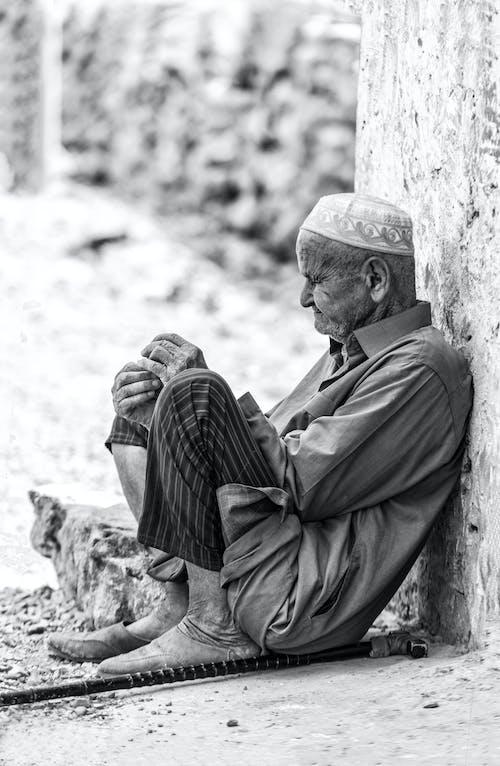 Mann In Der Schwarzen Anzugjacke Und In Den Schwarzen Und Weißen Streifenhosen, Die Auf Felsen Sitzen
