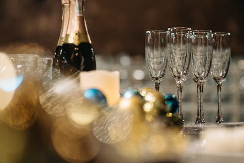 Close Up Photo of Champagne Bottles and Wine Glasses