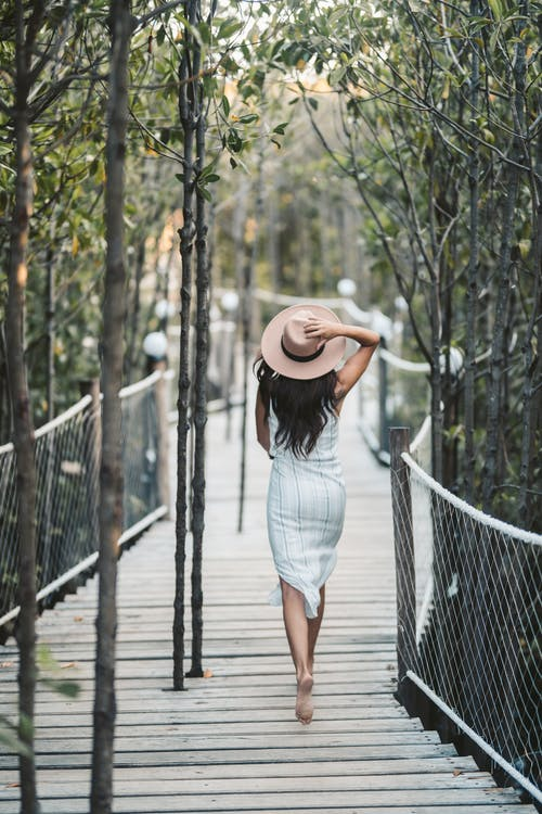 Woman In Striped Dress With Sunhat Walking Barefooted On Wooden Bridge