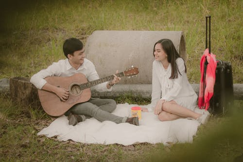 Man and Woman Playing Acoustic Guitar Sitting on White Textile