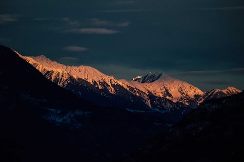 Rocky mountains with snowy peaks under blue sundown sky