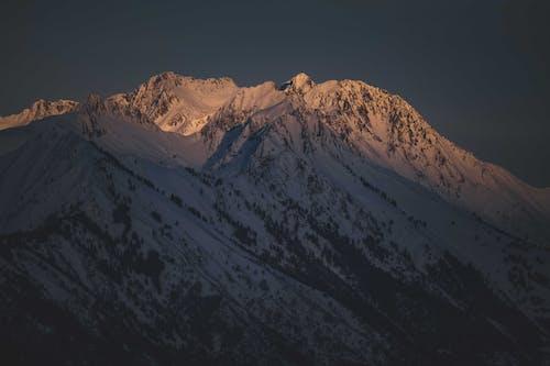 Scenic snowy mountain landscape under blue sundown sky