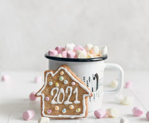 Festive gingerbread cookie with inscription 2021 placed against mug of delicious hot drink garnished with sweet marshmallows and served on white table