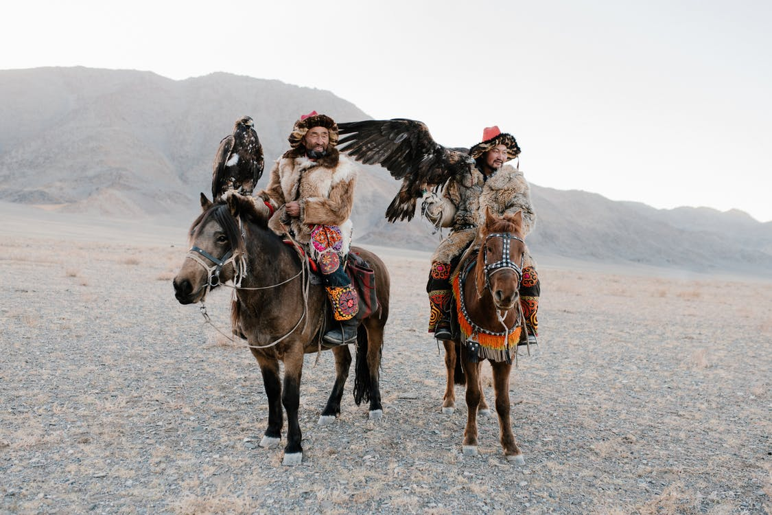 2 Men Riding Horse on Brown Sand