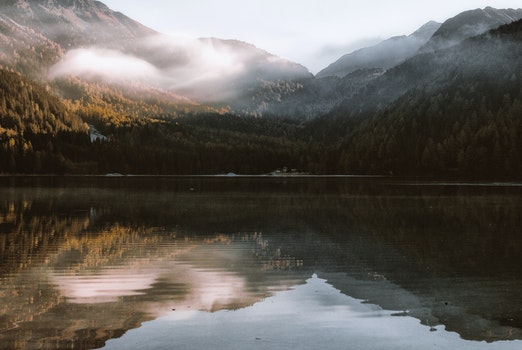 Mountain Reflection on Body of Water Under White Sky at