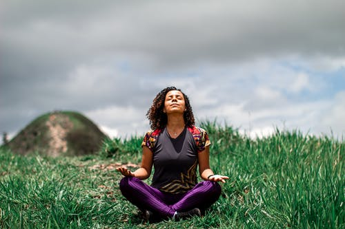 Woman in Black Tank Top and Purple Pants Sitting on Green Grass Field