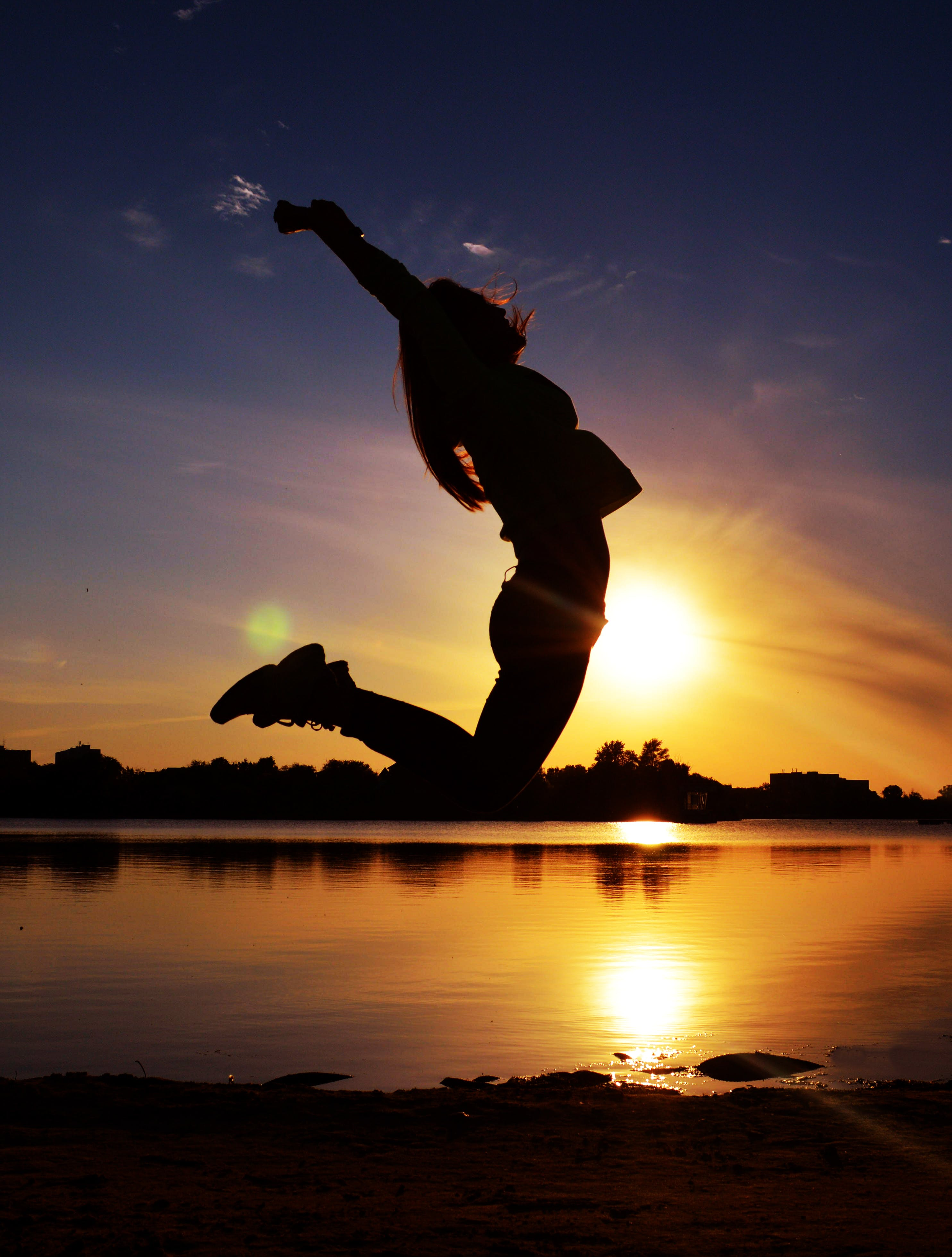 Woman Jumping Near Body of Water