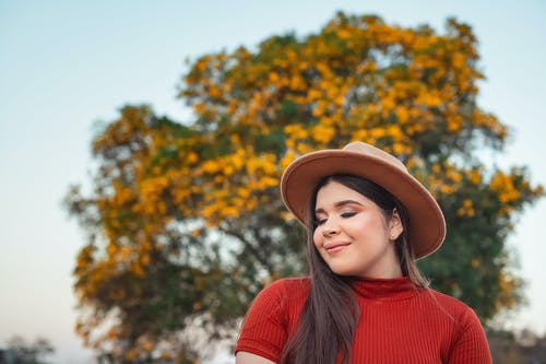 Woman in Red Sweater Wearing Brown Fedora Hat