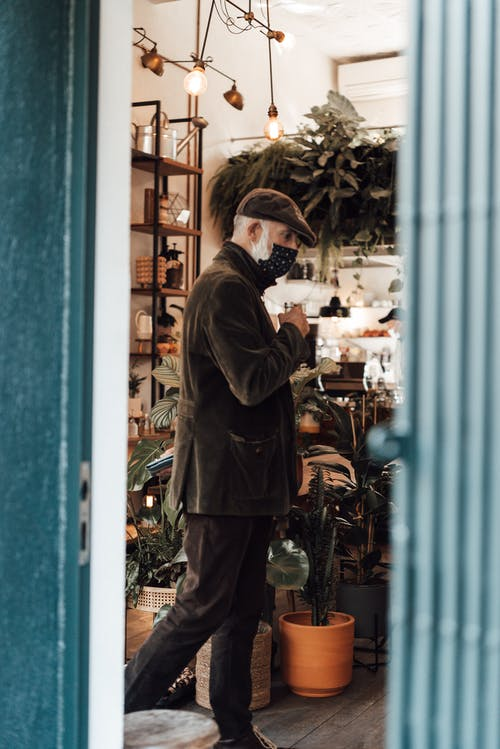 Senior man entering shop with potted plants