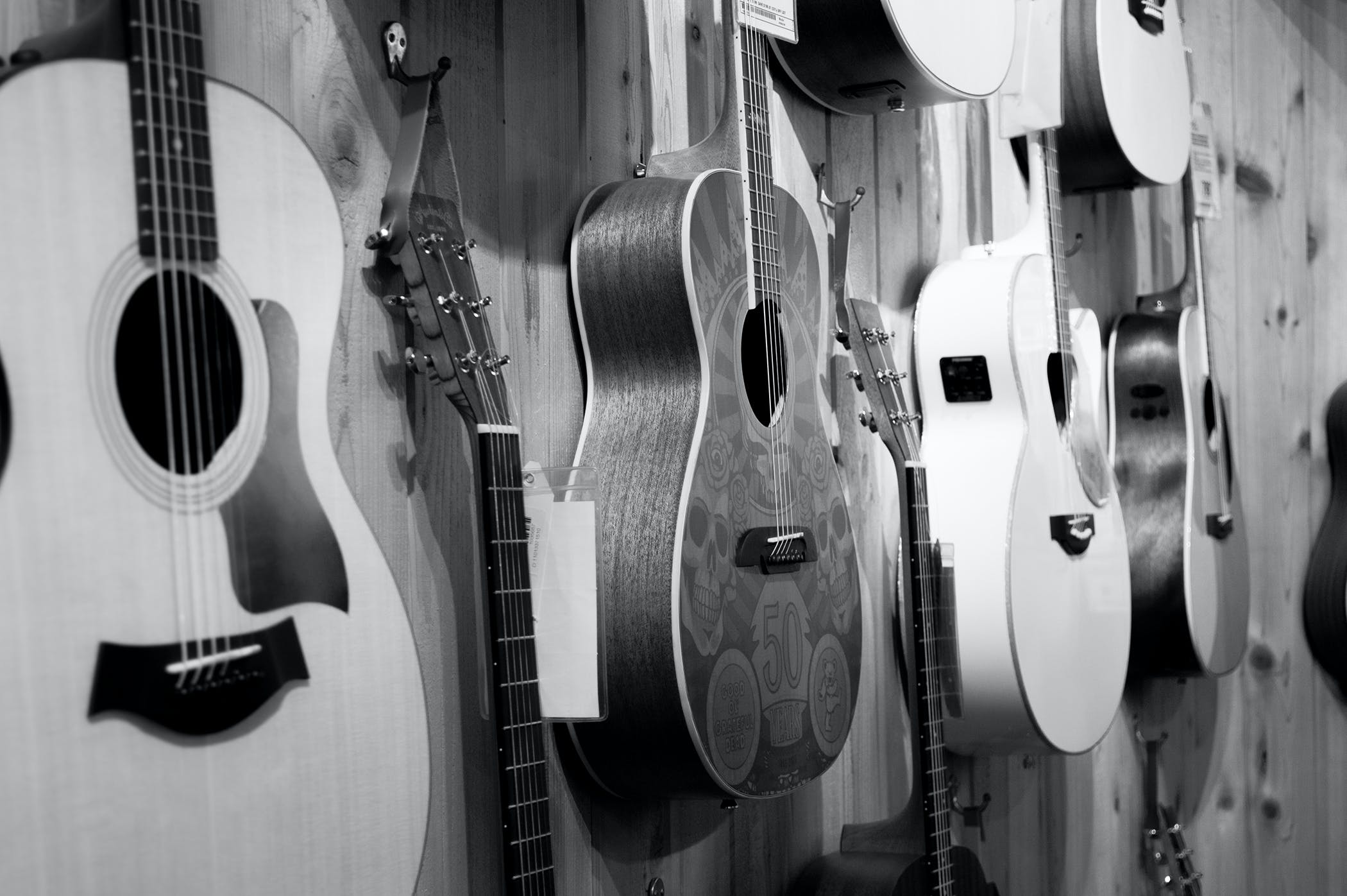 Gray Scale Photo of Acoustic Guitars
