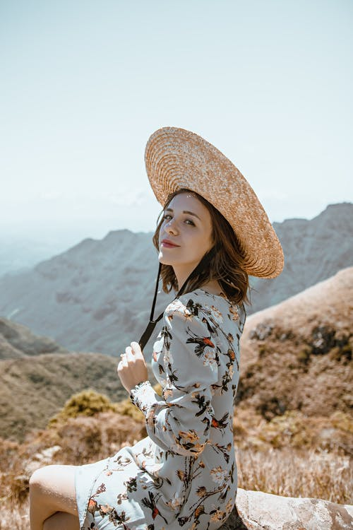 Dreamy young lady recreating on stone and admiring mountains in sunlight