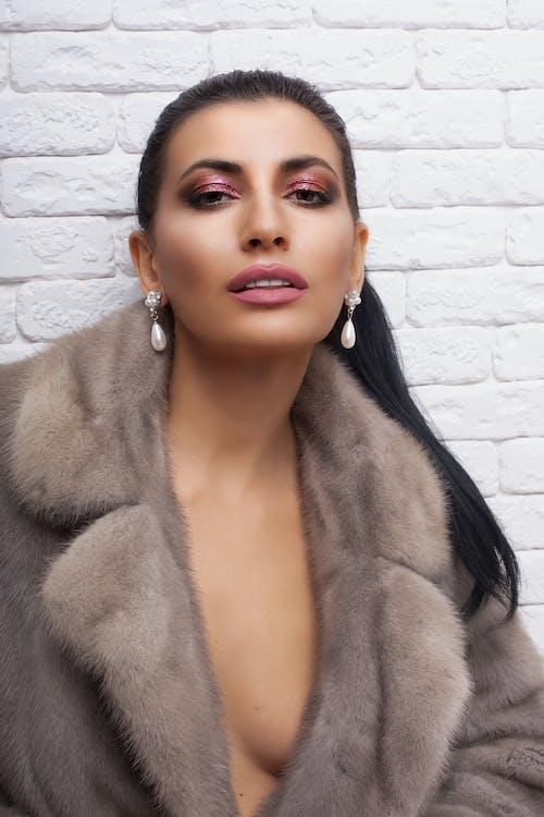 Stylish model in pearl earrings against brick wall